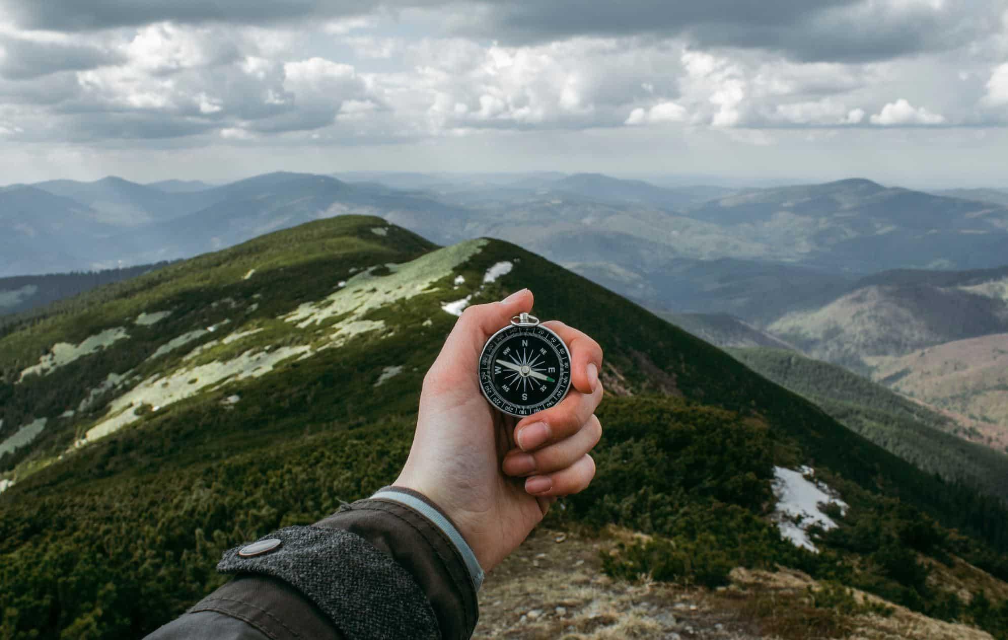 main tendue avec boussole sur une destination montagneuse