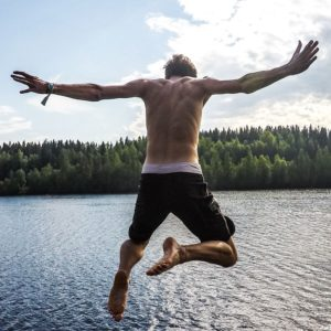 Man-jumping-from-a-pier-into-water